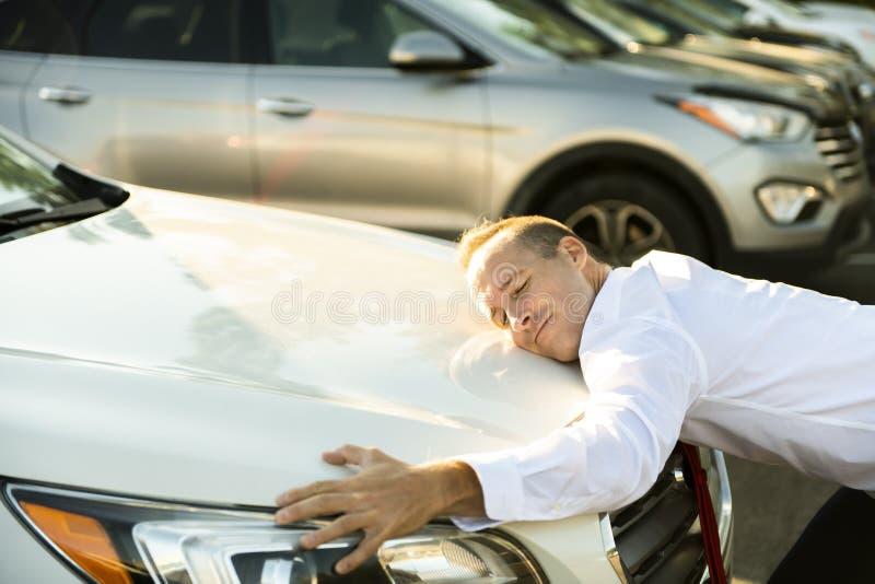 Car seller man hugging car at the garage. A Car seller man hugging car at the garage stock photography
