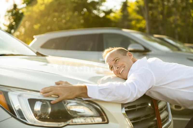 Car seller man hugging car at the garage. A Car seller man hugging car at the garage stock images