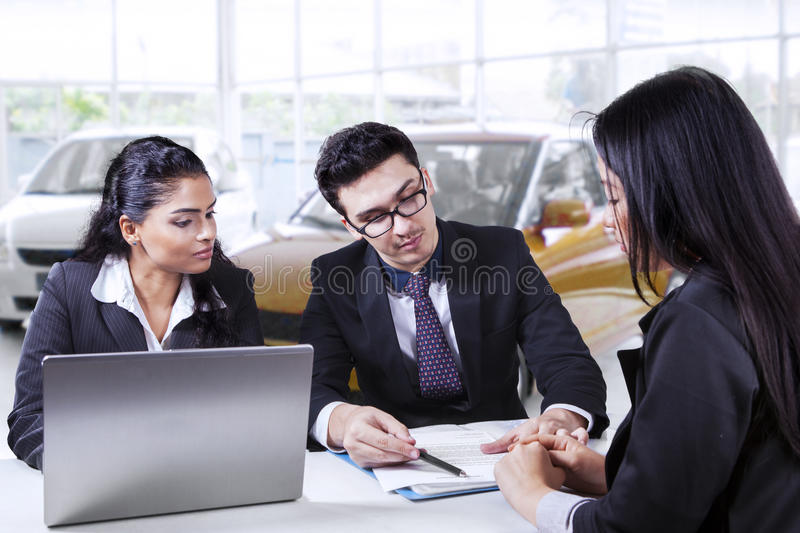Car seller showing credit document. Portrait of two young car sellers showing a credit contract for new car on their buyer in the showroom stock image