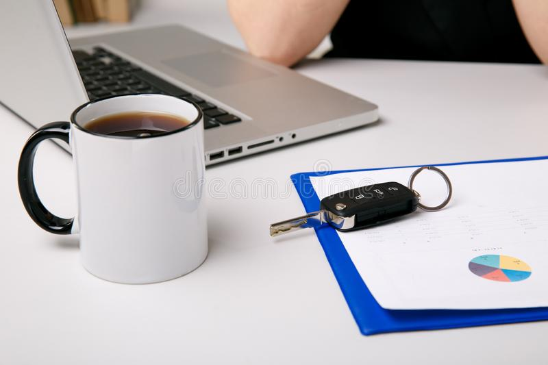 Car selling concept. Documents with keys on the desk. Cup of coffee and computer. stock image