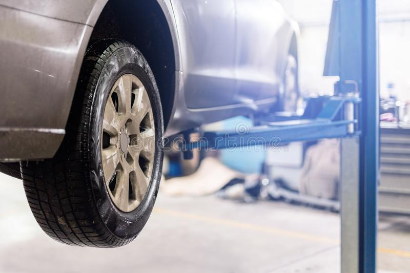 Car at service center. Vehicle raised on a lift. Check up, maintenance and repair concept royalty free stock photography