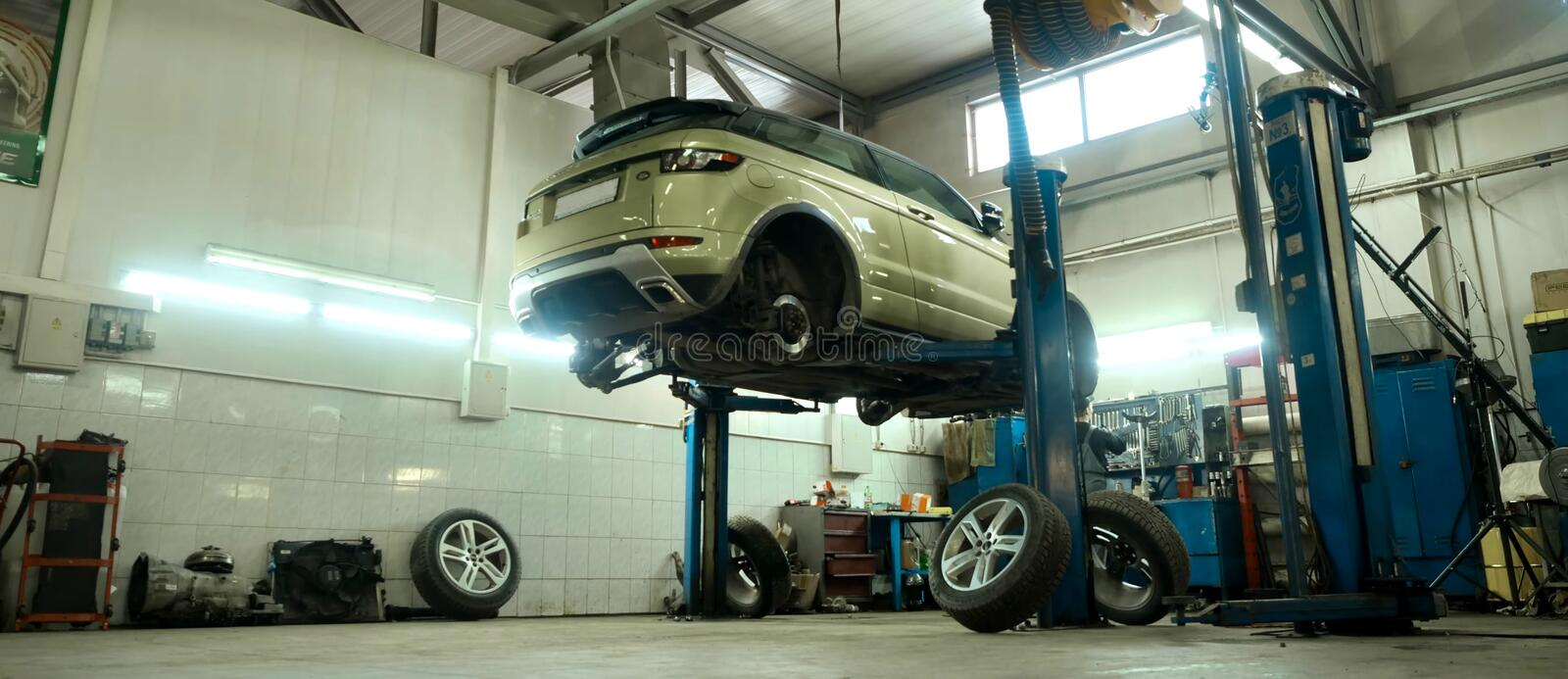 Car service center. Vehicle raised on lift at maintenance station. Auomobile repair and check up. stock photos