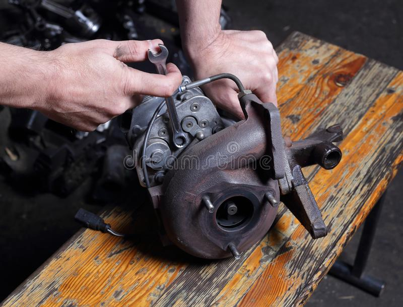 Car service - Engine repair mechanic hands with wrench Centrifugal  compressor nut. Car service - Engine repair, mechanic hands with wrench turns off Centrifugal royalty free stock photos