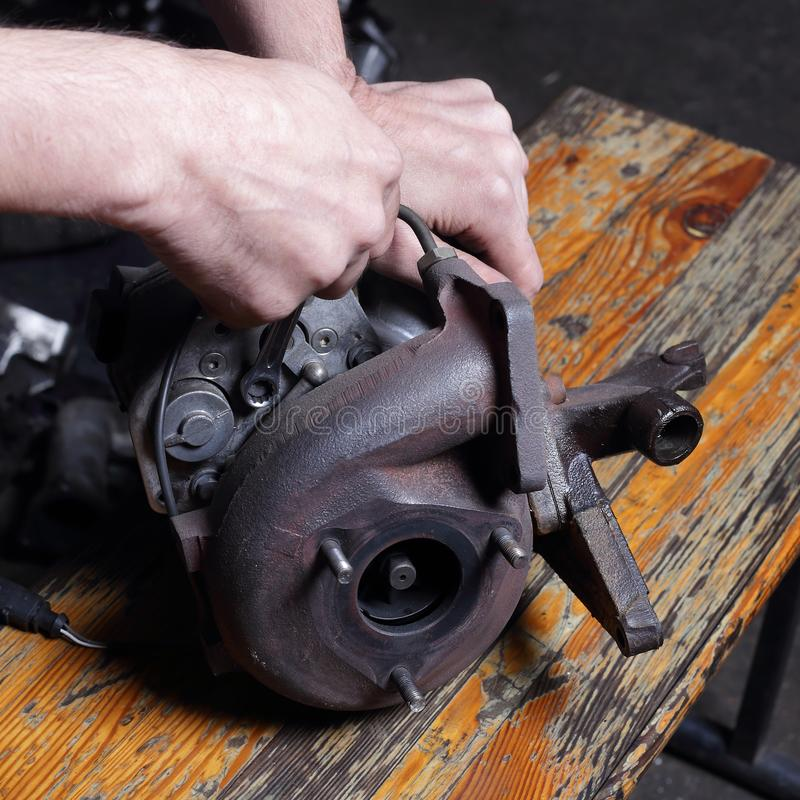 Car service - Engine repair mechanic hands with wrench Centrifugal compressor nut. Car service - Engine repair, mechanic hands with wrench turns off Centrifugal royalty free stock photo