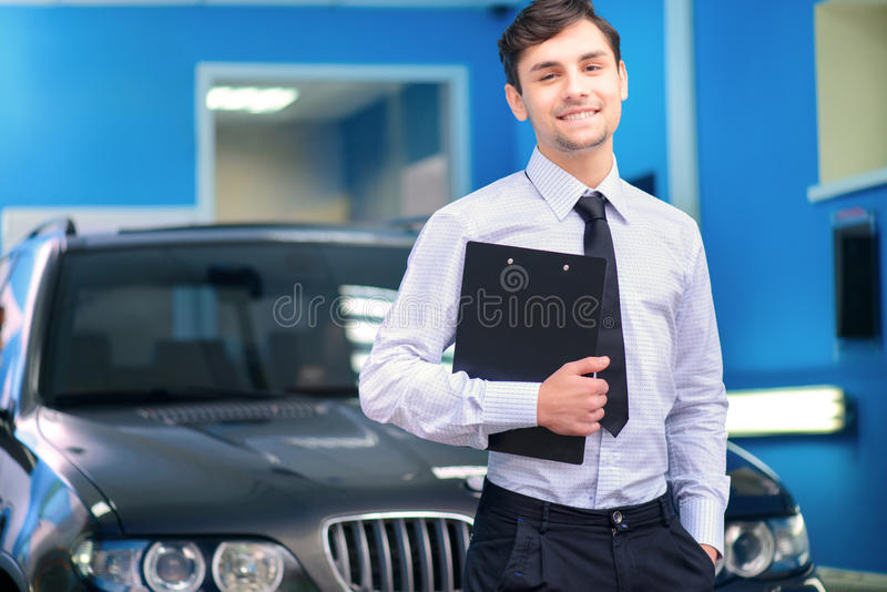Car service manager posing with a clipboard. Helpful and client oriented. Portrait of a handsome smiling car assistance manager in formalwear standing by the stock photos