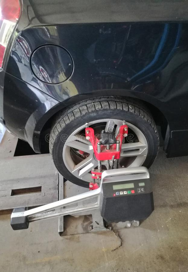 The car in service needs to align the wheels. wheel alignment is required. The car in service needs to align the wheels. peridodic verification stock image