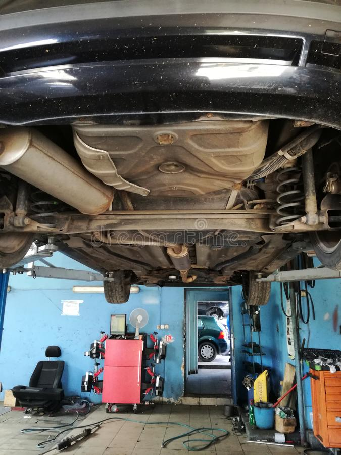 Car in service, raised on high-capacity hydraulic jack. Workers are in charge of car maintenance and repair royalty free stock photo