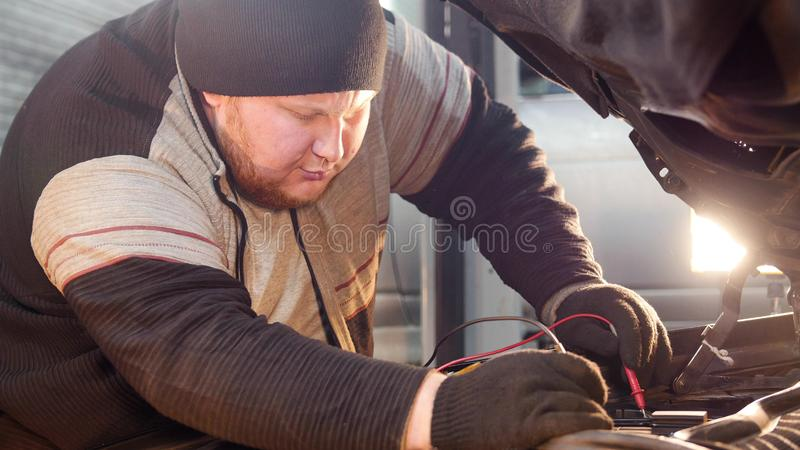 Car service. Thick ginger mechanic man checks the voltage with a multimeter royalty free stock images