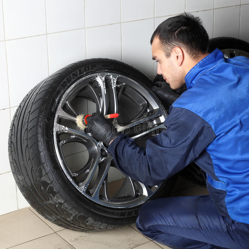 Car service. The worker washes rims royalty free stock image