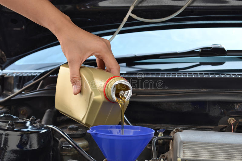 Car servicing mechanic. Pouring oil to engine stock photo