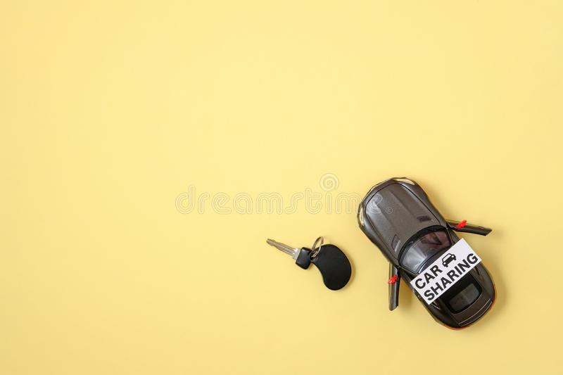Car sharing service concept. Car model, text sign. `CAR SHARING` and car key on yellow background. Top view, minimal flat lay style composition. Banner mockup royalty free stock image