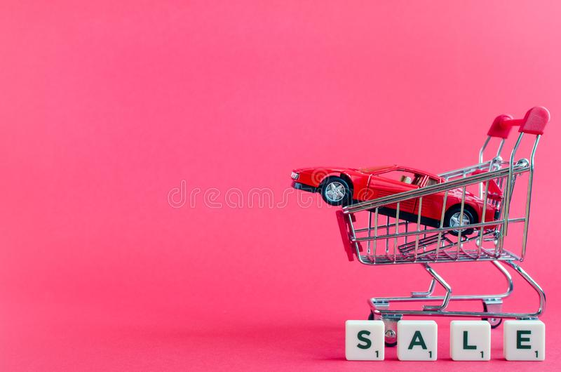 Car shopping, new car in a shopping cart. Car sale shopping concept. New red car in a shopping cart as a symbol for car buying and leasing. Pink background. Copy stock image