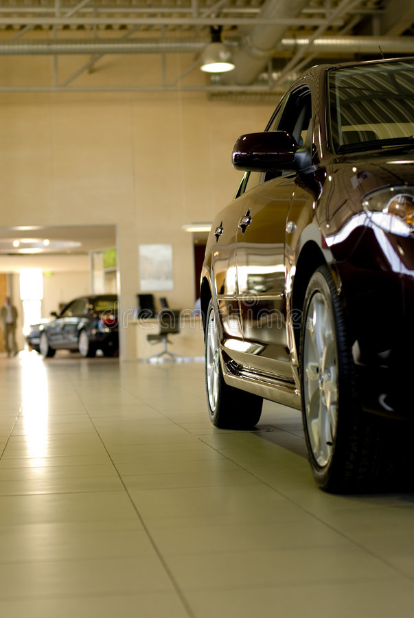 Car in showroom. Black car in showroom, with images reflecting off shiny doors royalty free stock images