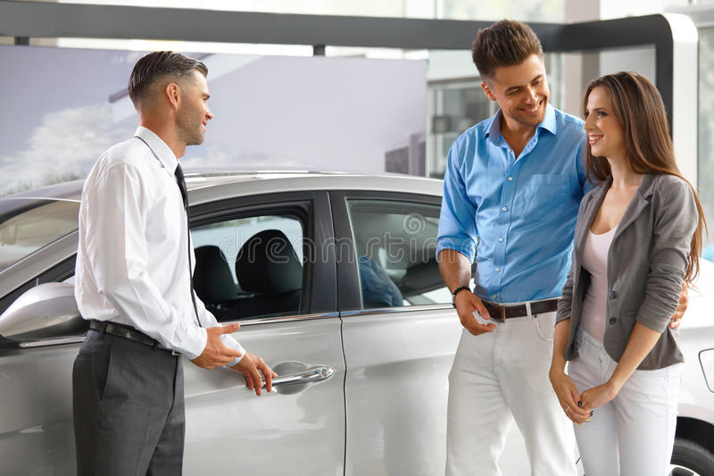 Car Showroom. Young Couple Buying a New Car at Dealership royalty free stock photos