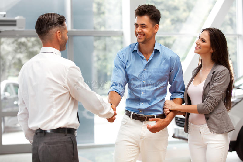 Car Showroom. Young Couple is Meeting with Seller in Auto Salon stock image