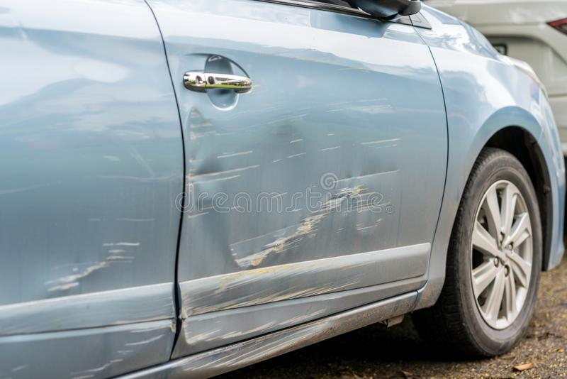 Car side is scratched and scraped with deep damage to the paint stock photography