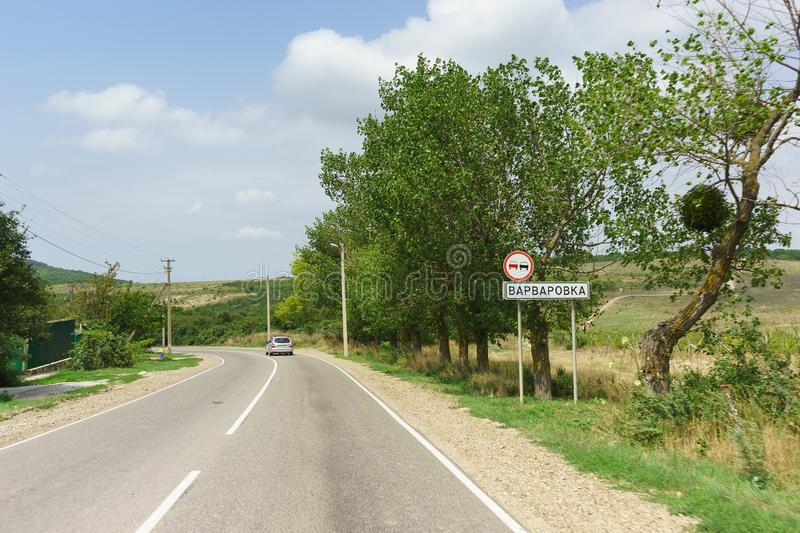 Car sign Overtaking is prohibited and the inscription in Russian Varvarovka. Entrance to the seaside village of Anapa district. Summer Sunny day royalty free stock images