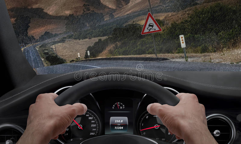 Car slipping on a road in the rain. Alongside the road is a sign for slippery road. Rain splashed windshield.  royalty free stock images