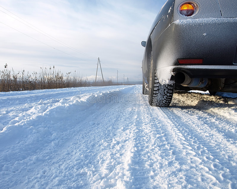 Car on a snowy country road stock images