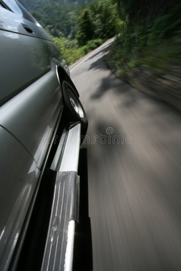 Car at speed. A car through the woods on a road turning right at speed royalty free stock photo