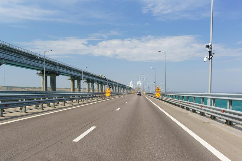 Car speed limit signs and road narrows due to maintenance repairs. Crimean bridge stock image