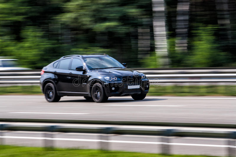Luxury BMW speeding on empty highway stock photography