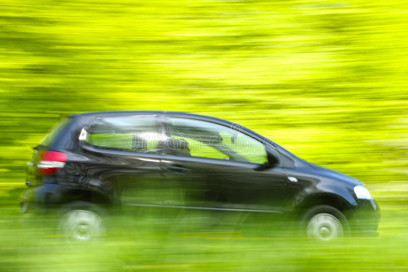 Car speeding. With motion blur (moving the camera royalty free stock photography