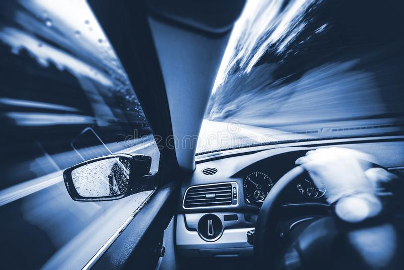 Car Speeding Concept. Photo. Men Driving His Car. Speeding on the Mountains Road. Duotone Blue Color Grading royalty free stock images