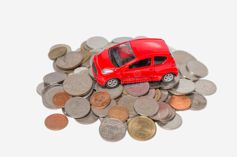 A car stand on a pile of coins. Isolated on white background royalty free stock photos