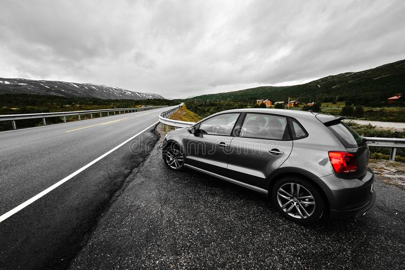 Grey modern car is parking next to a rural paved road which leads through the nature of Norway as far as the eye can see stock photo