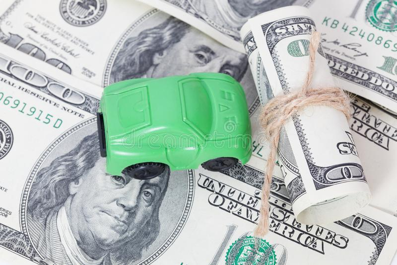 Car stands on dollar banknotes. cost of buying a car, fuel, insurance and other car costs. Car stands on dollar banknotes. cost of buying a car, fuel, insurance stock images