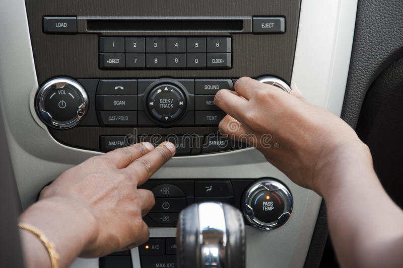 Car stereo. Two ladies playing with the car stereo system royalty free stock photo