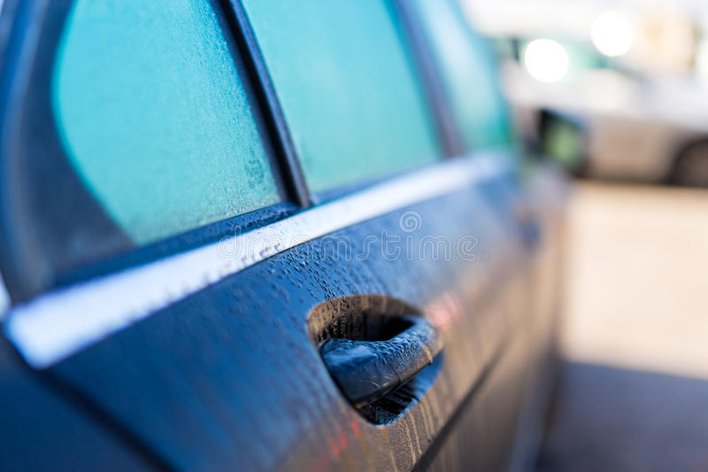Car on the street covered by rain. Shallow depth of field. Car after the rain. Water drops on the door stock image