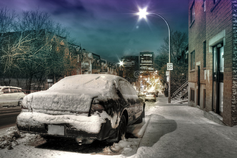 Car in the street at night. A car under the snow in a street at night royalty free stock photos