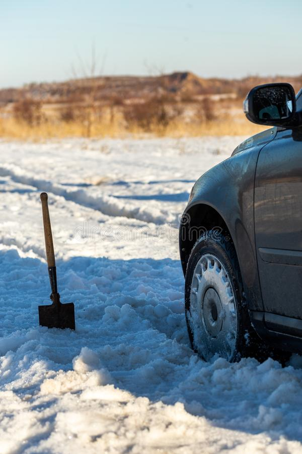 Car stuck in snow offroad at daylight with shovel and selective focus. Car stuck in snow offroad at daylight with shovel and selective royalty free stock image