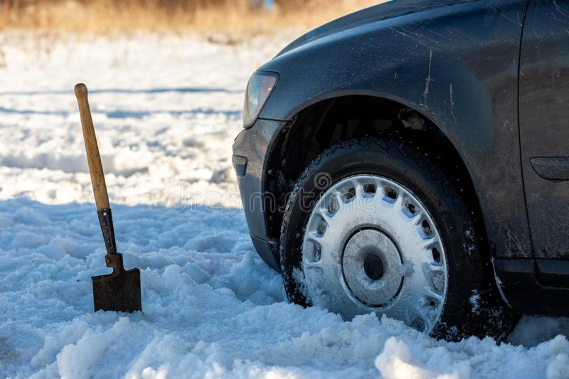 Car stuck in snow offroad at daylight with shovel and selective focus.  royalty free stock images