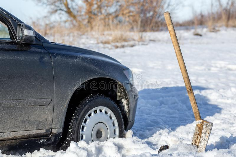 Car stuck in snow offroad at daylight with shovel and selective focus.  royalty free stock photo