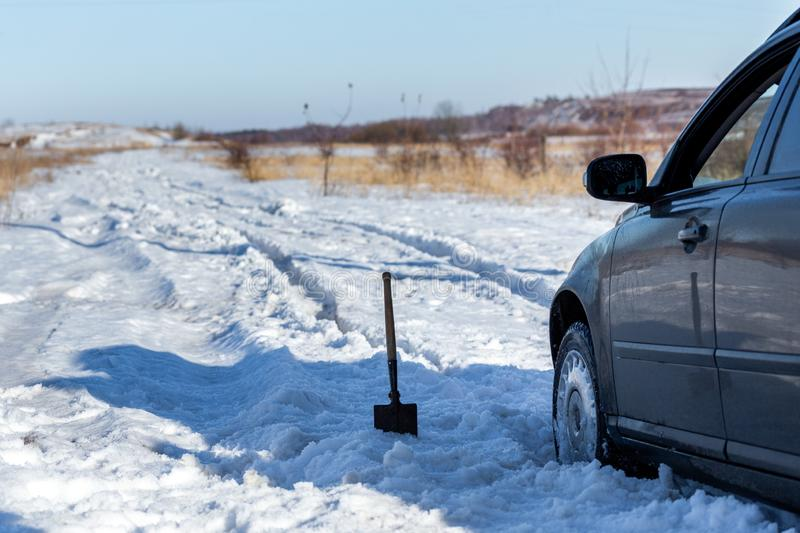 Car stuck in snow offroad at daylight with shovel and selective focus.  stock photography