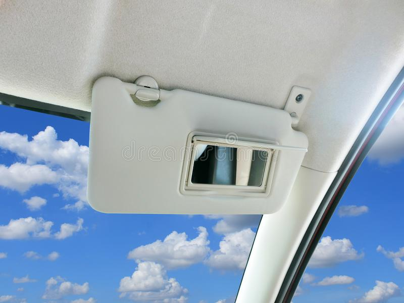 Car sun visor and mirror in car. Car sun visor and mirror in car with sky and clouds as a backdrop royalty free stock image