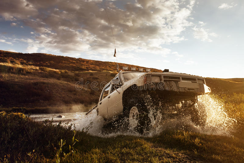 Car SUV overcomes water on the offroad background stock images