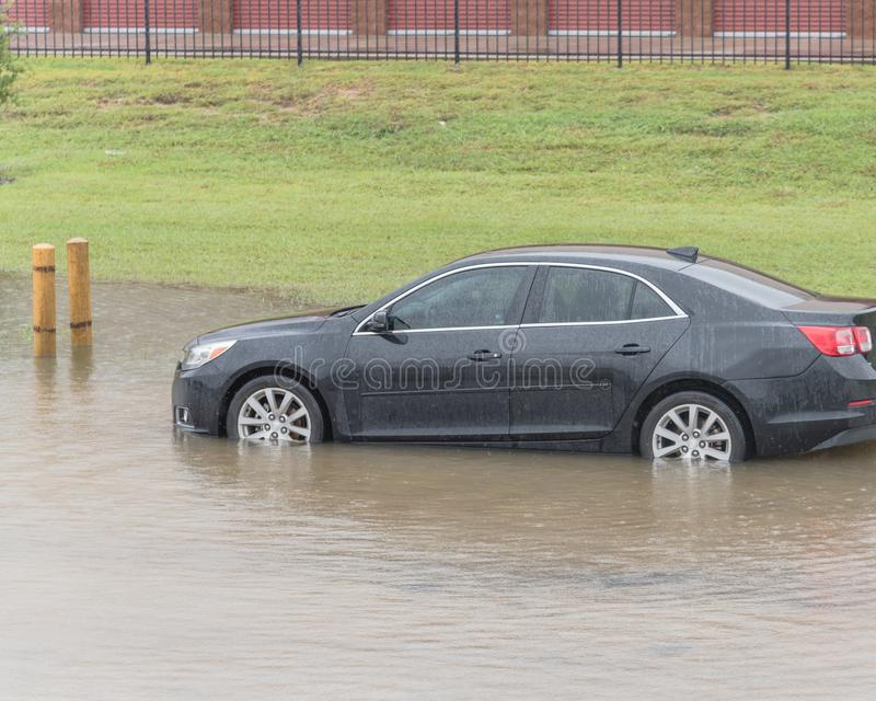 Car swamped by hurricane flood water in East Houston, Texas, USA. Black sedan car swamped by flood water in East Houston, Texas, US by Tropical Storm. Submerged royalty free stock images