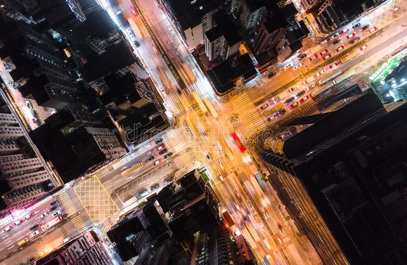 Car, taxi, and bus traffic on road intersection at night in Hong Kong downtown district, drone aerial top view. Asia city life royalty free stock image