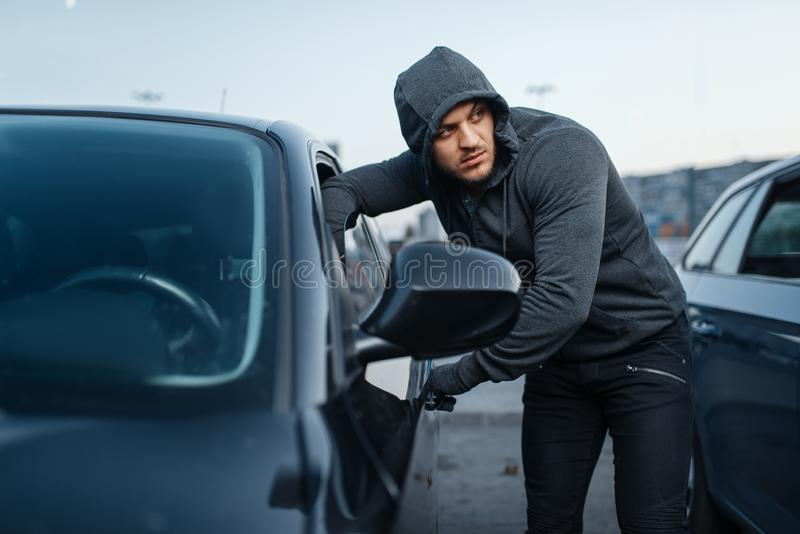 Car thief breaking door, criminal job, burglar. Stealing. Hooded male robber opening vehicle on parking. Auto robbery, automobile crime stock image
