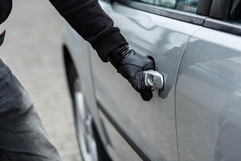Car thief hand pulling the handle of a car stock image