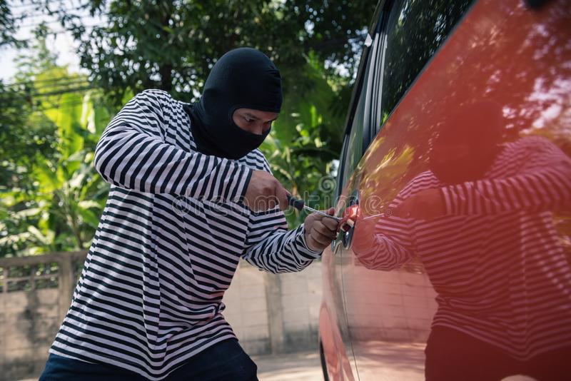 Car thief trying to unlock a car by screwdriver, Robber and thief concept royalty free stock photos