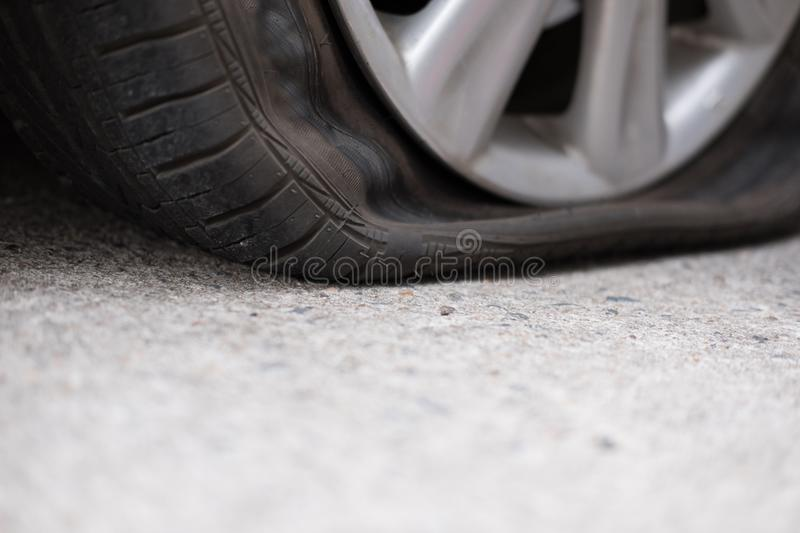 Car tire leak because of nail pounding. flat tyre on road. Flatt. En punctured auto wheel royalty free stock photography