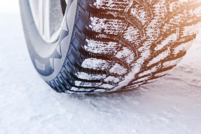 The car tire in the snow close up. Car tracks on the snow. Traces of the car in the snow. Winter tires. Tyres covered with snow at. Winter road. Soft lighting royalty free stock images