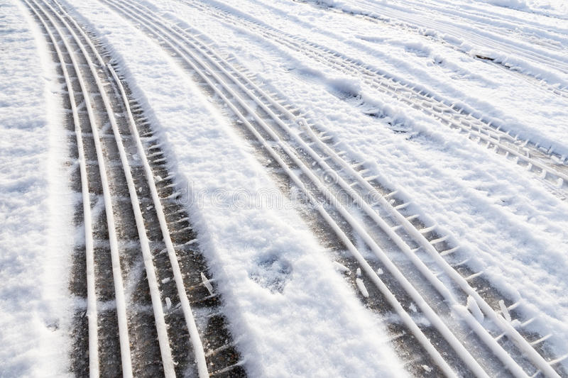 Car tire tracks in snow on street stock image