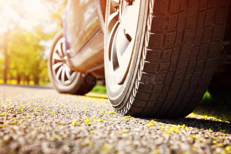 Car tires closeup on asphalt road on summer day at park royalty free stock photo