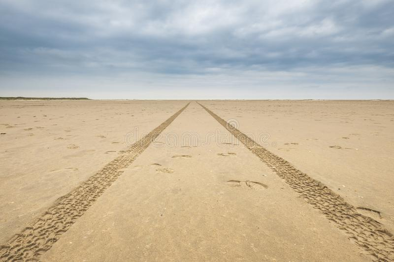 Tire tracks on a deserted beach lead to the horizon stock photography